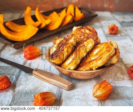 Pumpkin Pancakes In A Deep Plate And Slices Of Raw Pumpkin On An Oblong Wooden Tray On A Light Table