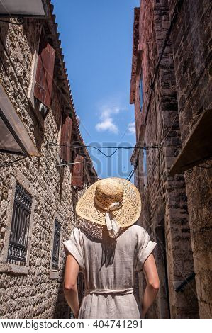 Rear View Of Beautiful Blonde Young Female Traveler Wearing Straw Sun Hat Sightseeing And Enjoying S