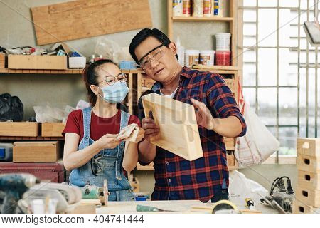 Experienced Carpenter In Goggles Discussing Quality Of Wooden Drawer Made By His Apprentice