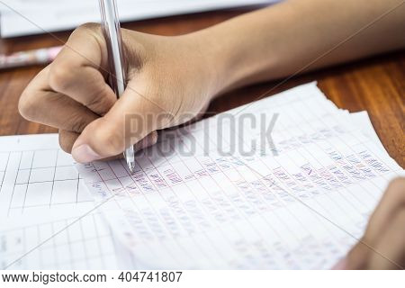 Teacher Or Researchers Checking Statistical In Document Paper On Questionnaires About Education And