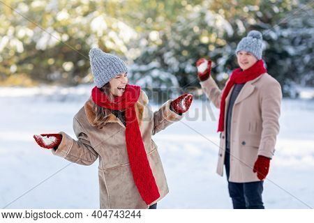 Cheerful Young Couple In Stylish Warm Outfits Having Snowball Fight Outdoors, Enjoying Snow At Winte