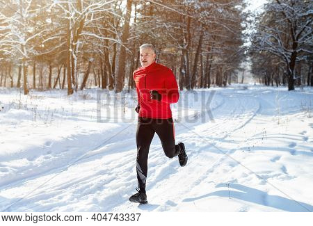 Athletic Mature Man In Sportswear Jogging At Snowy Winter Park. Healthy Senior Runner Sprinting Outd