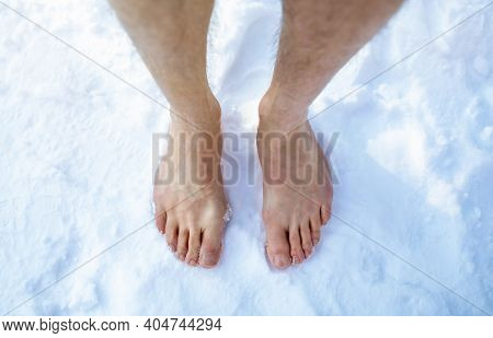 Top View Of Male Feet Standing On Snow Outdoors, Cropped. Unrecognizable Guy Making Cold Exposure Tr