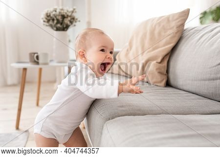Toddler Girl Laughing Having Fun Standing Near Sofa In Living Room At Home. Adorable Little Baby Mak
