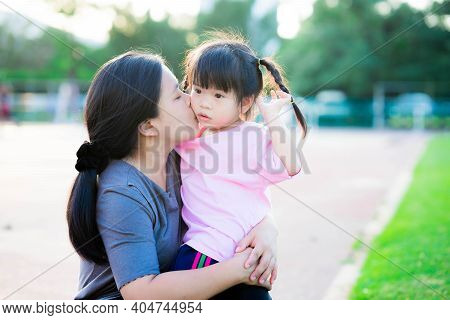 Mother Embraced Her Daughter And Lovingly Kissed Her Cheek. Daughter Is Touchy. The Evening Sun Shin