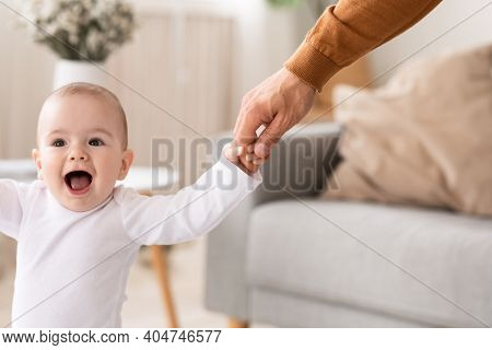 Baby Daughter Holding Dads Hand Learning To Walk And Stand, Daddy Helping Toddler Make First Steps A