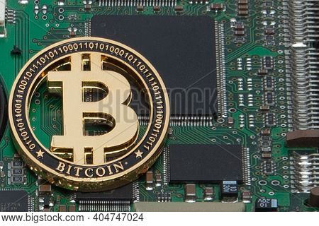 Close-up Of Gold Bit Coin, Computer Circuit Board With Bitcoin Processor And Microchips. Electronic