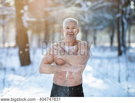Athletic Mature Guy Tempering His Body With Snow, Developing Resistance To Cold At White Winter Fore