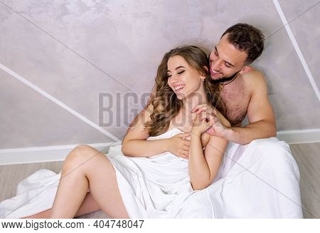 Man And Woman Covered By White Sheets. Naked Couple Draped In Sheet. Young Sexy Couple In Love Sitti