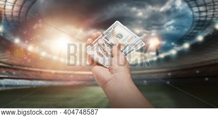 Close-up Of A Man's Hand Holding Us Dollars Against The Background Of The Stadium. The Concept Of Sp