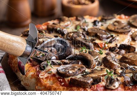 Closeup Of Slicing A Mushroom And Cheese Pizza With Fresh Thyme