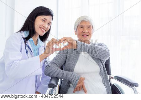 Happy Senior Woman Sitting On Wheelchair And A Young Nurse Doing Heart Shape Symbol With Hands. Disa