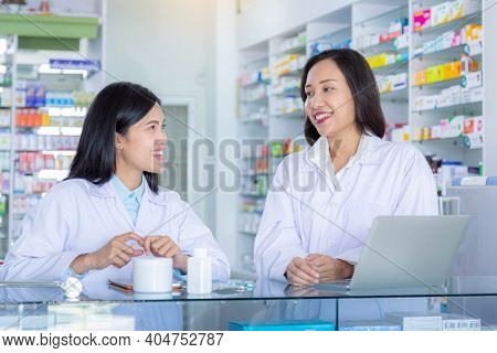 Two Smiling Asian Pharmacists At Drugstore. Medicine, Pharmaceutical, Health Care And People Concept