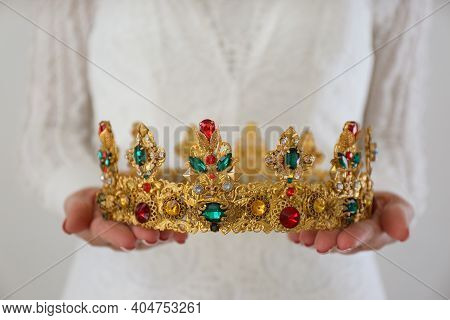 Woman Holding Beautiful Crown With Gems On Light Background, Closeup. Fantasy Medieval Period