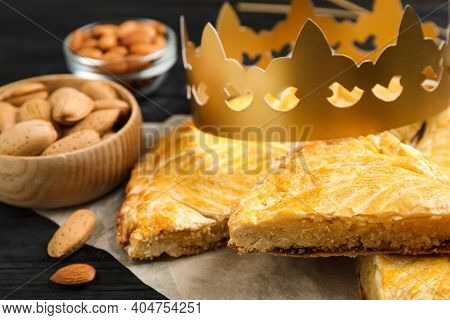 Traditional Galette Des Rois With Paper Crown On Black Wooden Table, Closeup