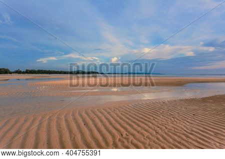 Tropical beach in ebb time in sunset lights