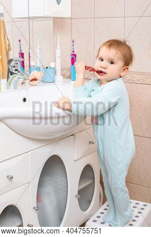 Baby girl wearing blue blanket sleeper learning to brush teeth in a bathroom