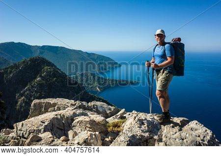 Hiking on Lycian way. Man with backpack posing for photo on rock cliff high above Mediterranean sea on Lycian Way trail, Trekking in Turkey, outdoor activity