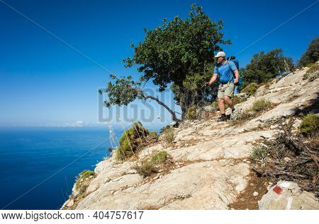Hiking on Lycian way. Man with backpack walking down on rock slope high above Mediterranean sea on Lycian Way trail, Trekking in Turkey, outdoor activity