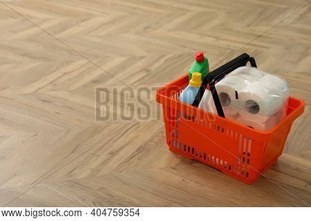 Shopping Basket With Household Goods On Wooden Floor. Space For Text