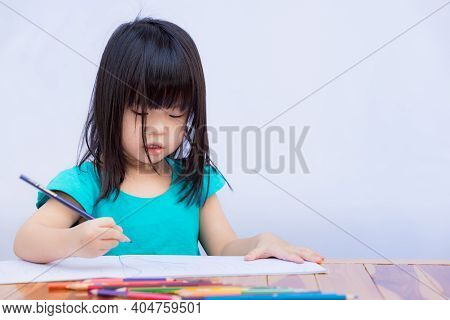 Cute Asian Girl Is Drawing An Art Class While Studying At Home. Children Have Hair Tress Blocking Th