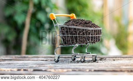 Manure On Mini Shopping Cart With Natural Light Background (business And Finance Concept)
