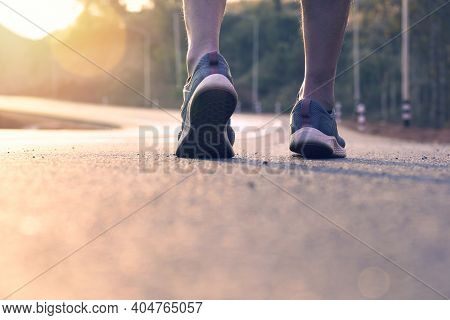 Athlete Running At Road , Close Up On Leg For Slow Walk For Warm Up Before Running At Sunset Evening