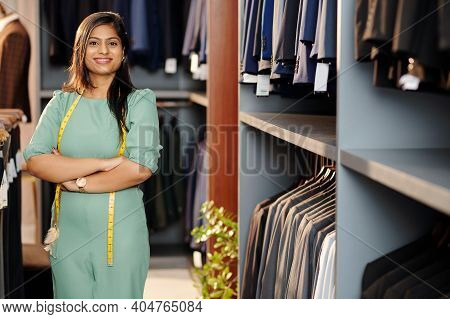 Portrait Of Cheerful Young Indian Shop Assistant Standing In Store With Arms Folded And Looking At C