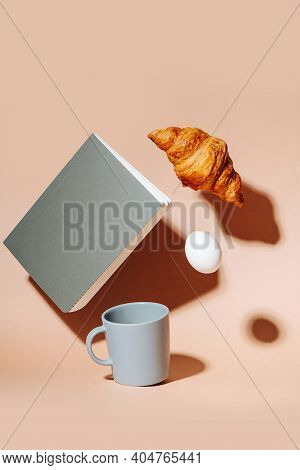 Coffee Mug On Peach Colored Surface. Croissant, Egg And Notebook Hovering In Air