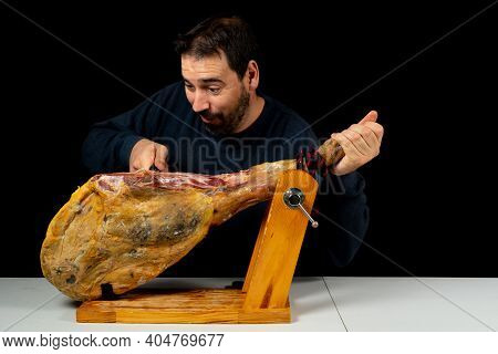 Bearded Man With A Ham Knife Ready To Cut A Piece Of Typical Spanish Ham Isolated On Black Studio Ba