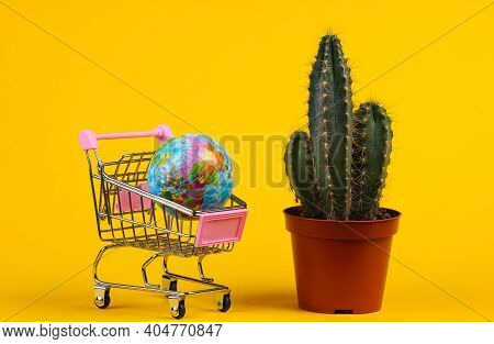 Global Shopping Concept. Cactus In Pot And Supermarket Trolley With Globe On Yellow Studio Backgroun
