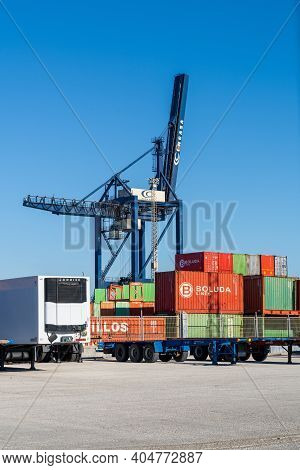 Harbor Crane And Containers And Tractor Trailers In The Industrial Port In Cadiz