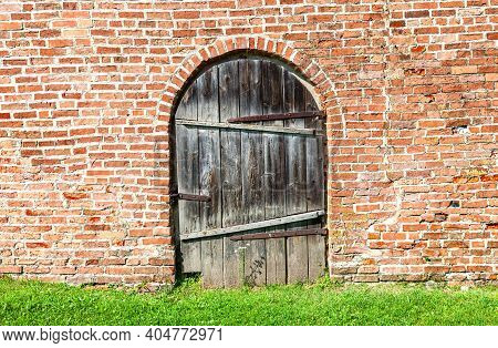Old Wooden Gate With Forged Massive Metal Hinges In The Brick Wall