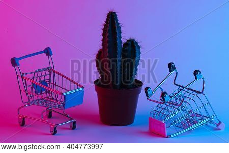 Cactus With Shopping Trolley In A Trendy Neon Light. Gradient Pink-blue Glow. Concept Art. Minimalis