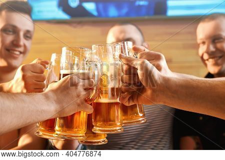 Selective Focus Of Glasses Of Beer In Hands Of Cheerful Male Friends In Pub. Male Company Resting To
