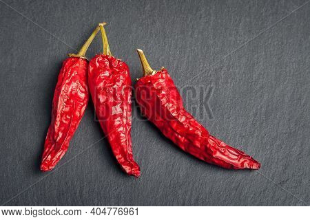 Red Pepper. Top View Of Three Red Dry Peppers Stacked On Black Shale Stone. Hot Chili Peppers. Spice
