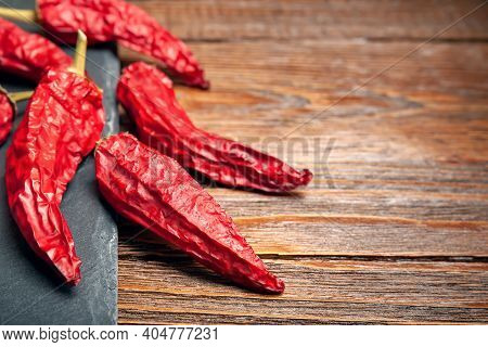 Red Pepper. A Pile Of Dried Red Peppers Stacked On A Black Slate Stone On A Wooden Surface. Hot Chil