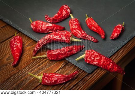 Red Pepper On A Slate Stone. A Pile Of Dry Red Pepper Lying On The Wooden Table. Hot Chili Peppers.