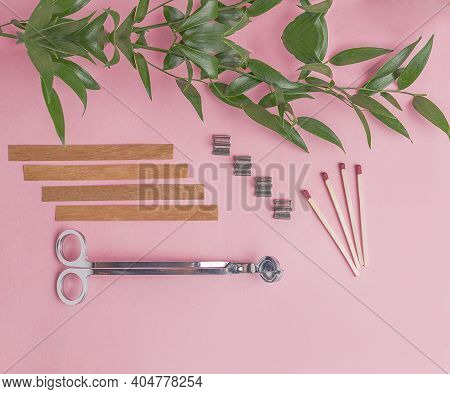 Flat Lay Of Wooden Wicks, Scissors And Wick Holders On Pink Background. Nearby Are Matches And A Bra