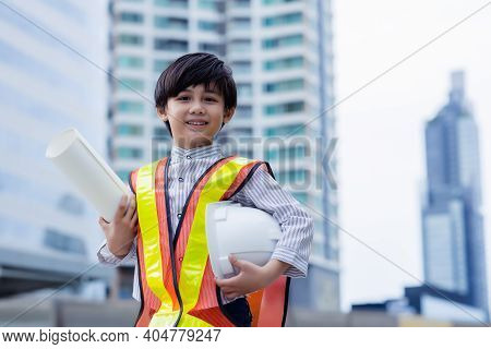 Little Engineer Boy Wear Protective Helmet And Holding Document Wearing Protective Workwear.  Smart