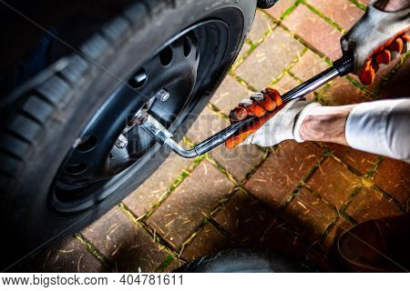 Male Hands Using A Lug Wrench. Changing A Car Tyre.