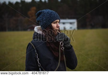 Young Breeder In Winter Clothes Blows A Dog Whistle To Summon A Stray Dog. Authentic People. Binary
