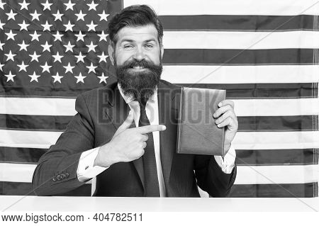 Turn Attention. American Businessman Pointing Index Finger At Book. Pointing At Usa Flag Background.
