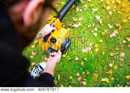 Starting A Handheld Leaf Blower In A Garden To Cleaning A Lawn.