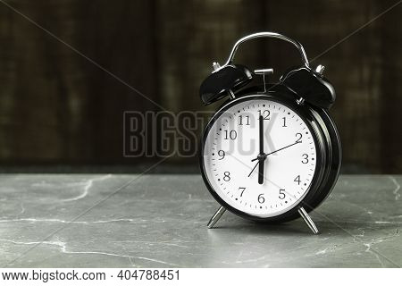 The Black Alarm Clock Hands Point To Six O'clock. Clock And Alarm Clock On The Table With Space For
