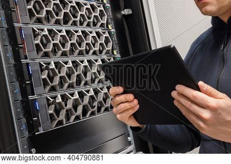 Male Computer Engineer With Digital Tablet Examining Hardware In Datacenter