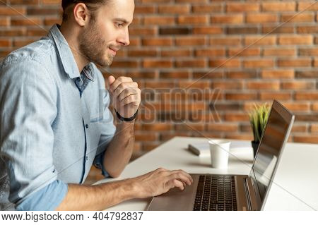 A Handsome Friendly Hipster Using Laptop Indoor. Young Freelancer Looks At The Screen With Interest,