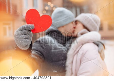 Valentine's Day Concept, Loving Couple Kiss And Hug At A Winter Snowy Park. Young Man Holds A Red Pa