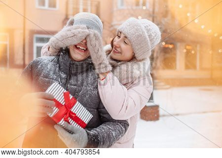 Young Romantic Woman Closes Boyfriend's Eyes With Her Hands In Woolen Mittens To Make A Surprise Out