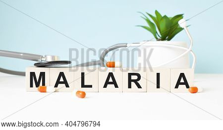 The Word Malaria Is Written On Wooden Cubes Near A Stethoscope On A Wooden Background. Medical Conce
